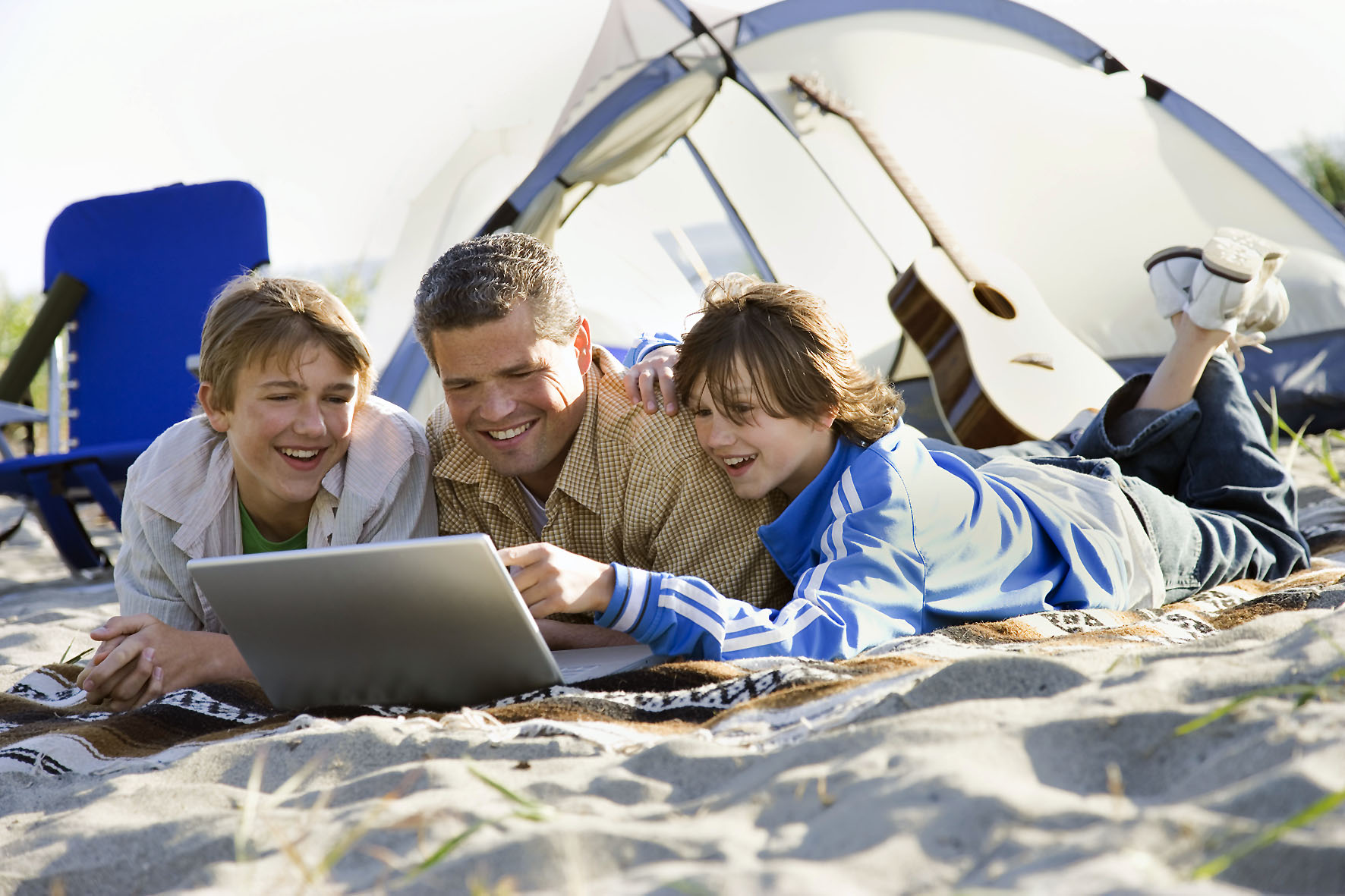 PC aufräumen Father and Two Sons Using Laptop on Beach